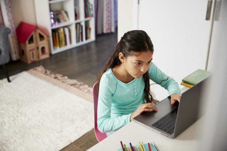 Young Girl Sitting At Desk In Bedroom Using Laptop To Do Homework