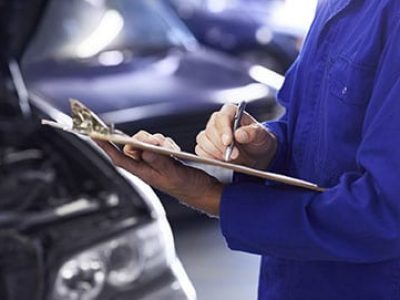 Close up of a car mechanic doing a check list on his clipboard